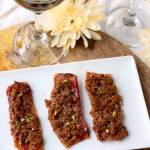 View of a rectangular white plate with three strips of Nutty Maple Brown Sugar Bacon Appetizer on a wooden serving tray. In the background a wine glass filled with white white. Next to it there is a cream flower and another wine glass.