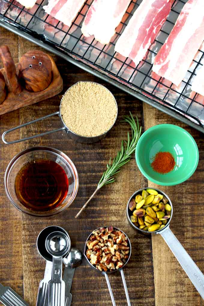 View of ingredients sitting on a wooden counter. Thick cut bacon on a rack over a sheet pan, measuring cups with brown sugar, chopped pecans and pistachios, A small bowl filled with maple syrup and another one with cayenne pepper and a sprig of fresh rosemary.