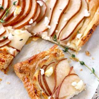 View of a golden brown puff pastry tart sliced The tart is topped with thinly sliced pears garnished with goat cheese and fresh thyme on a parchment paper lined baking sheet.