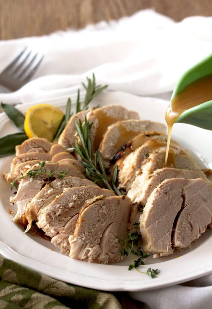 A platter with slices of turkey breast garnished with rosemary, thyme and a slice of lemon/ From the top a small green gravy boat pours gravy