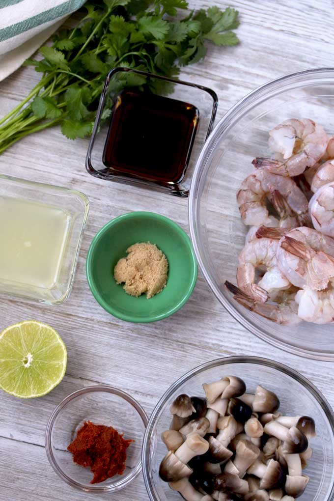 View of ingredients for Thai Tom Yum Soup on a white wooden board. Fresh raw shrimp with the tails on. Lime juice, fish sauce, brown sugar, Thai red chili paste, straw mushrooms and fresh cilantro.