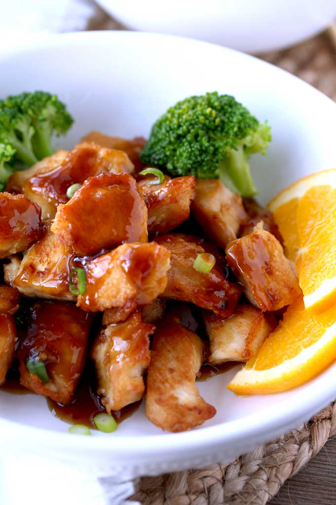 Close up view of easy Orange Chicken garnished with orange slices on a white bowl