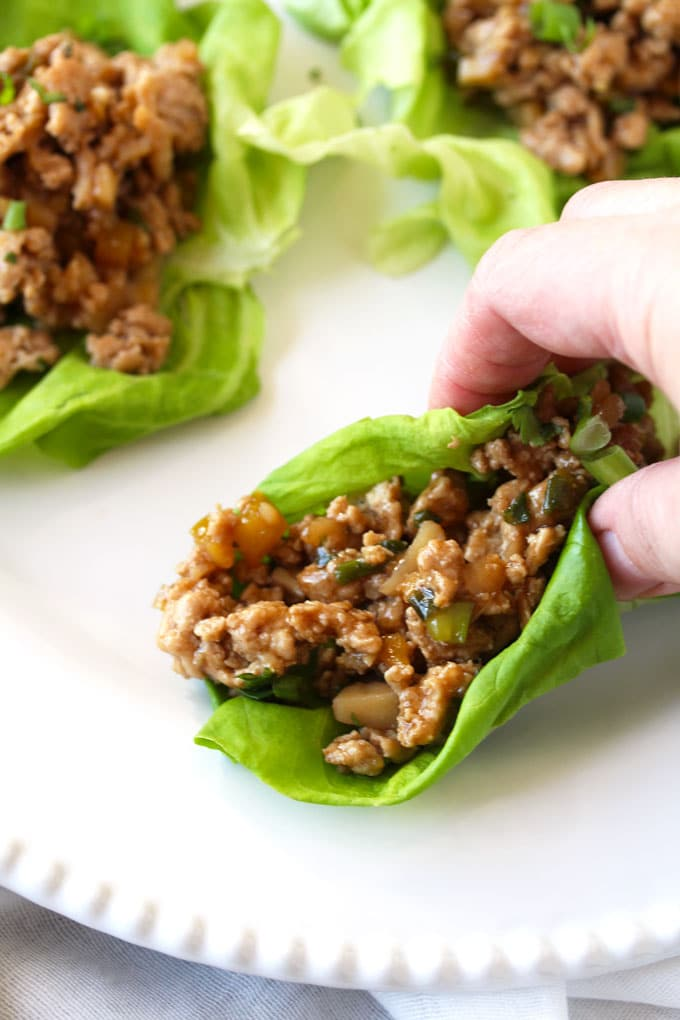 Pictured here a wrap ready to be eaten. Asian Chicken Lettuce Wraps recipe