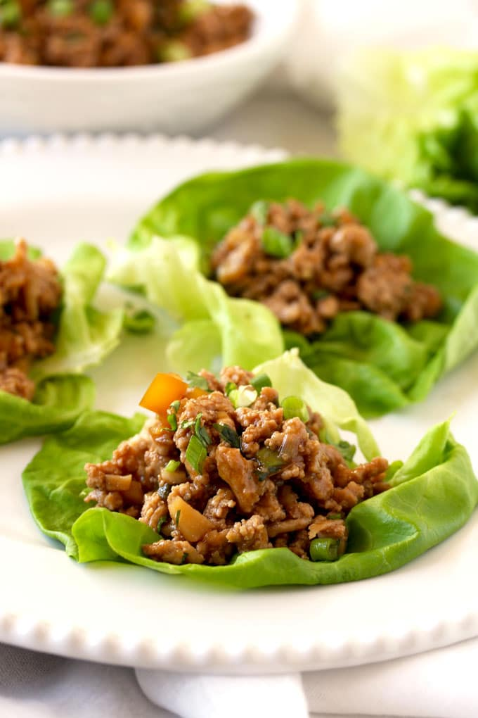 Pictured here a close up view of the Asian chicken lettuce wrap filling on top of a butter lettuce leaf