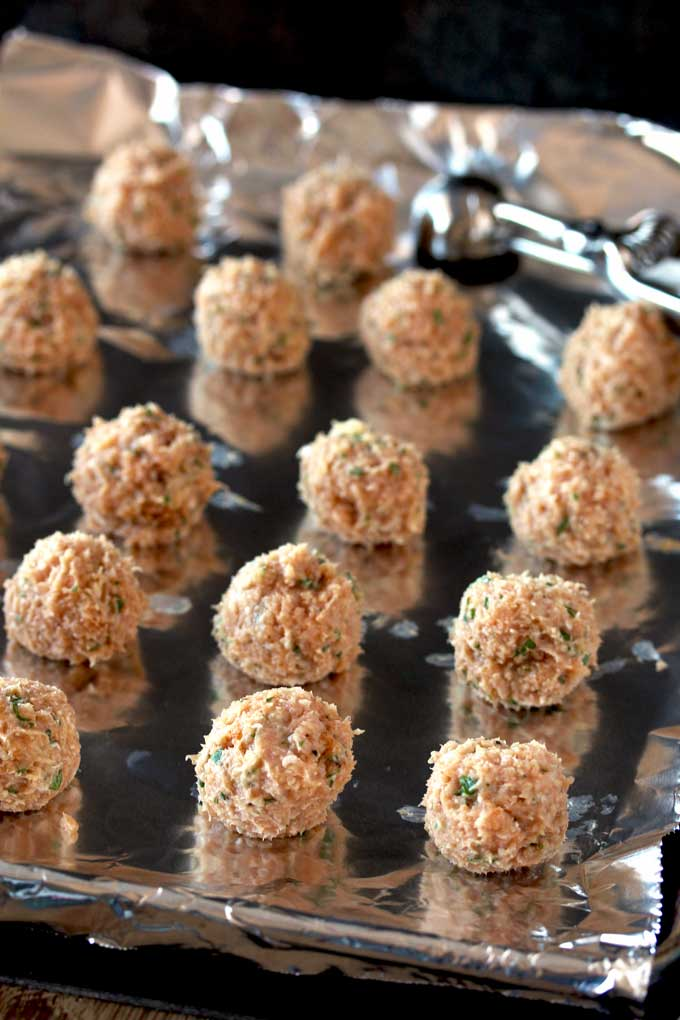 Pictured here raw Cajun chicken meatballs on an aluminum foil lined baking sheet.