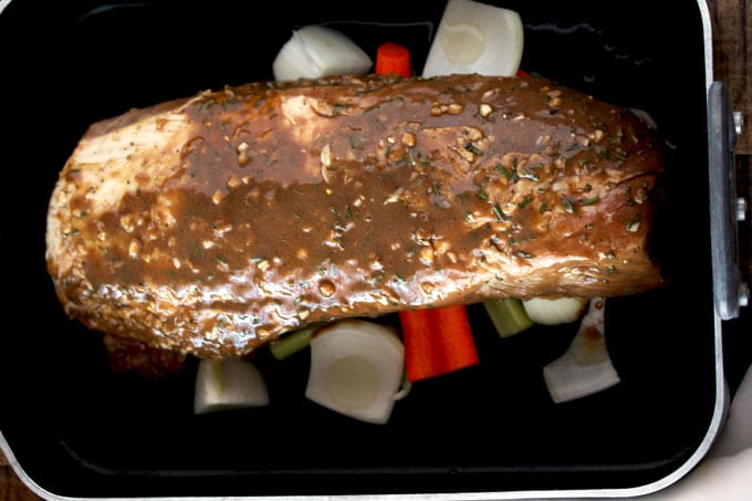 A raw pork loin roast sitting on top of carrots, onions and celery inside a roasting pan