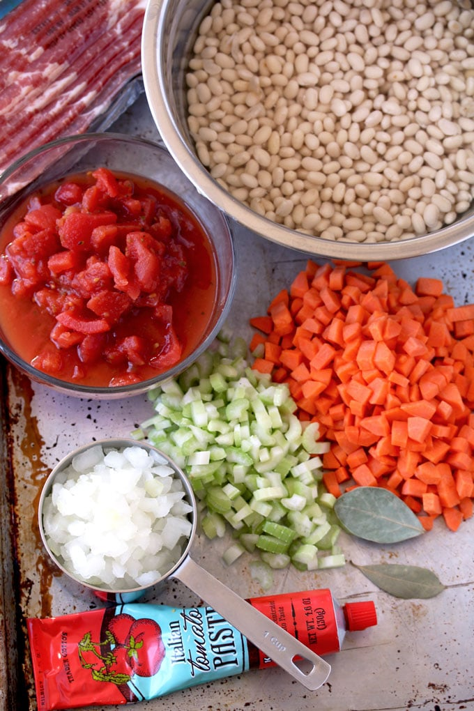 Pictured here are the ingredients for making Bean and Bacon soup. White beans, chopped carrots, celery and onions. Diced tomatoes, tomato paste, bacon and bay leaves.
