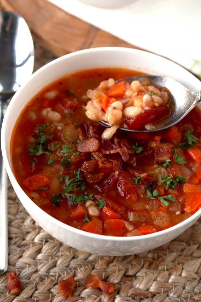A spoon is scooping Bean and Bacon Soup from a white bowl.