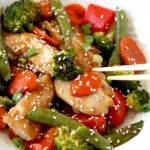 Pictured here a white bowl filled with Asian Chicken and vegetables Stir Fry garnished with sesame seeds and sliced green onions.