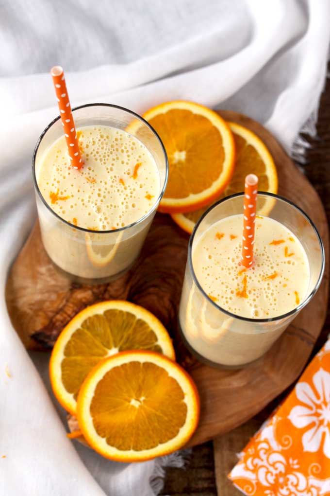 Top view of two glasses filled with Orange Honey Lassi