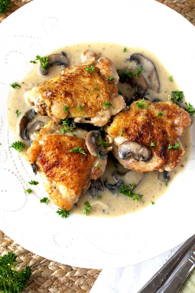 Top view of 3 pieces of creamy chicken with mushrooms served on a white plate