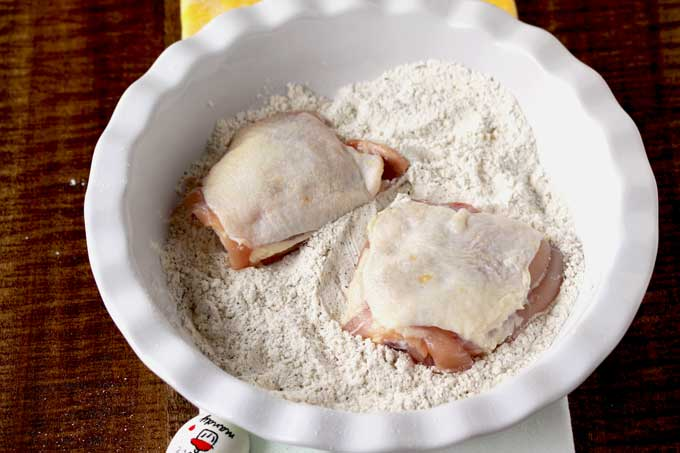 A shallow bowl with seasoned flour and a couple of raw chicken thighs