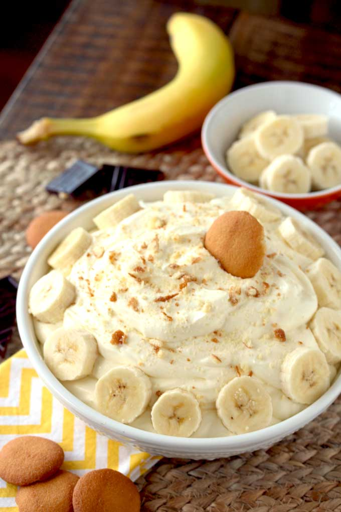 A bowl of fluffy and creamy banana cream pie dip garnished with sliced bananas and topped with nilla wafer crumbs
