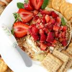 A round of baked brie cheese with nuts topped with strawberries and surrounded by crackers on a white plate.
