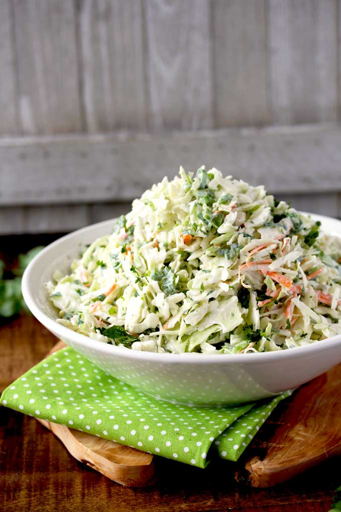 A bowl with a heaping serving of Creamy Cilantro Lime Coleslaw.