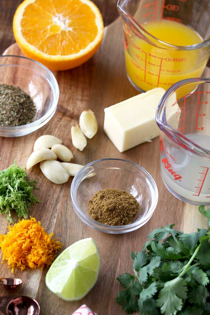 Ingredients to make Mojo Chicken on a wooden board. Lime juice, orange juice, orange and lime zests.=, cilantro, garlic, cumin, oregano and butter.