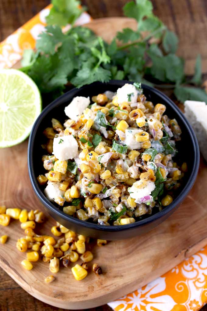 Top view of a black ceramic bowl filled with Mexican street corn Salad