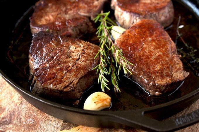 Four filet mignon steaks in a cast iron skillet
