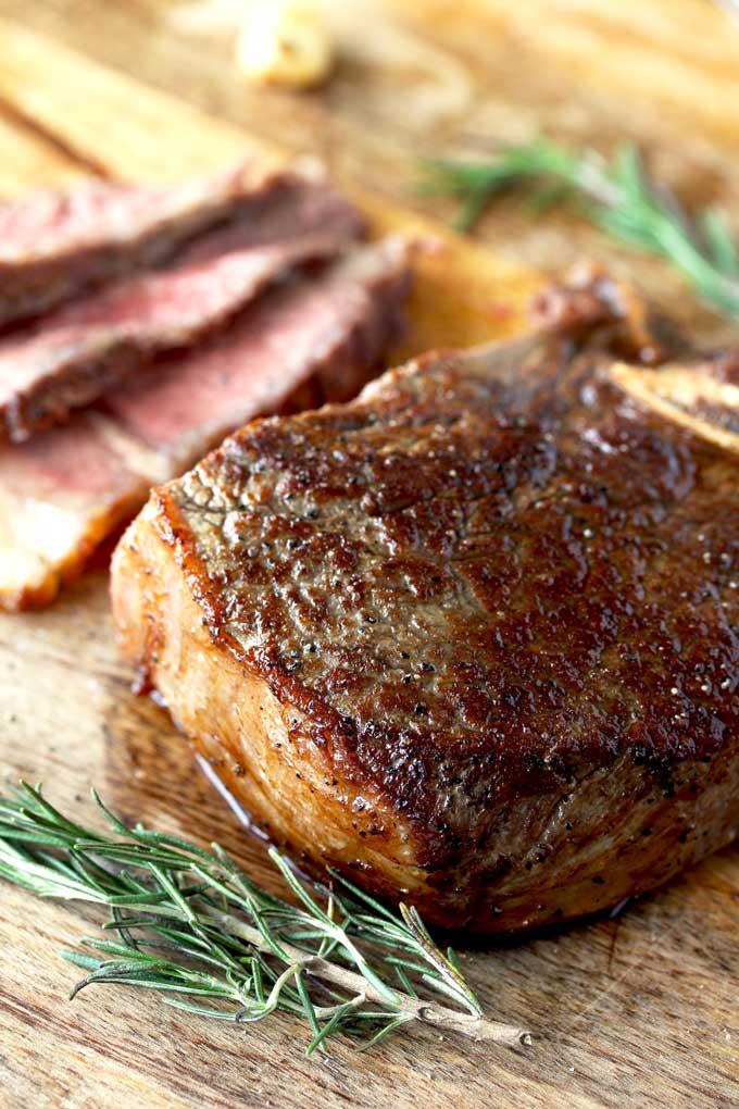 Golden brown pan seaed steak on a cutting wooden board.