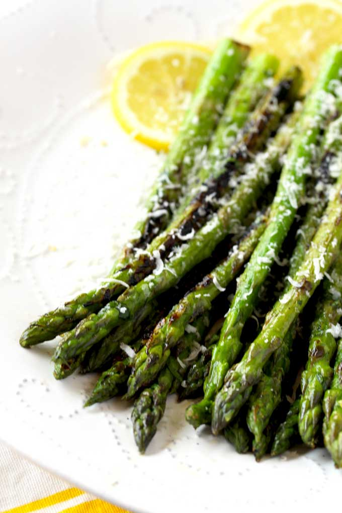 Grilled Asparagus tossed in lemon garlic butter and sprinkled with Parmesan cheese on a white plate