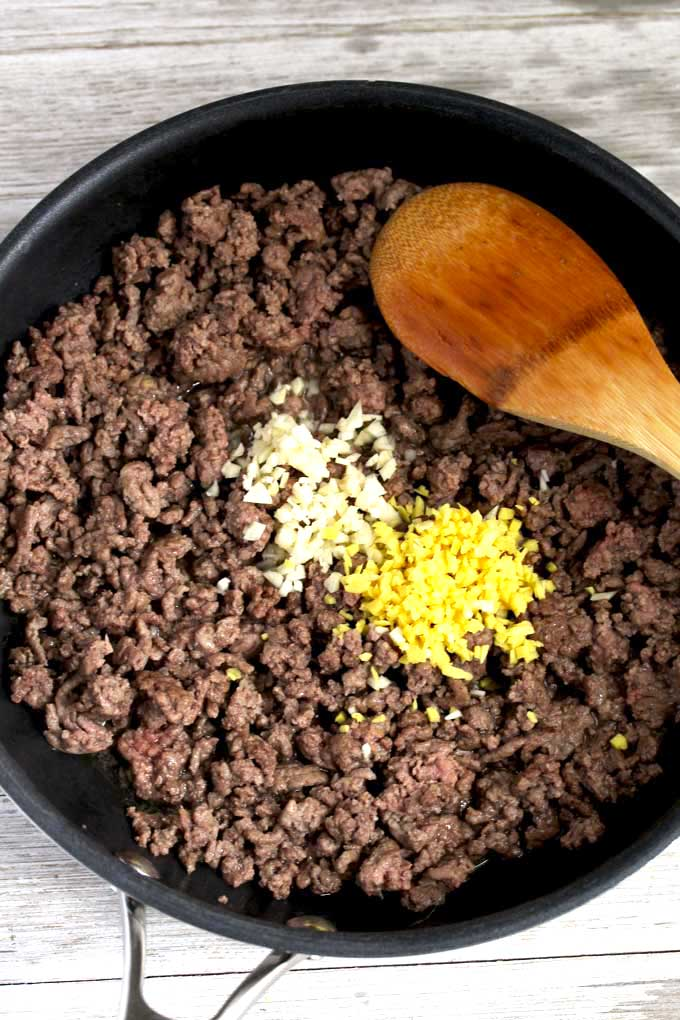 Ground beef, chopped garlic and ginger in a skillet.