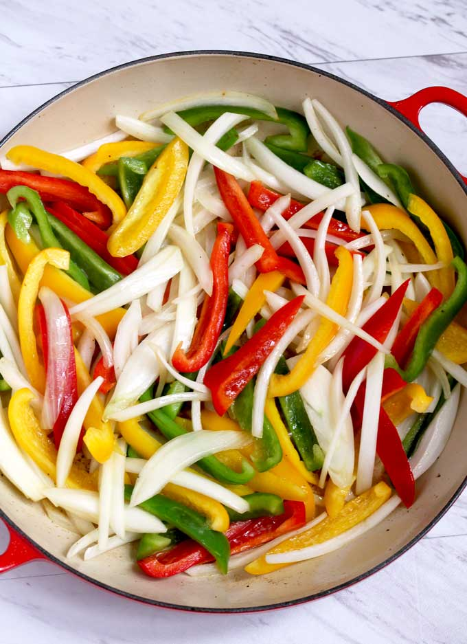 Onions and bell peppers sauteing in a skillet.