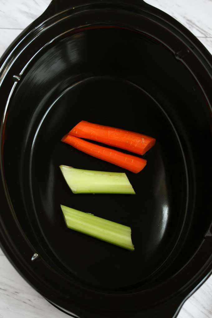 Carrots and celery inside a slow cooker.