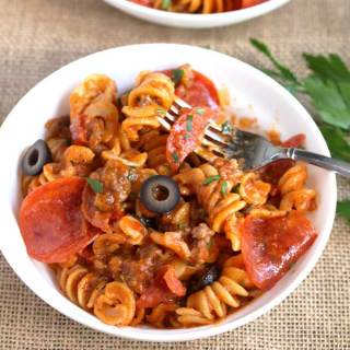 Pizza Pasta with pepperoni, sausage, olives and cheese in a white bowl.