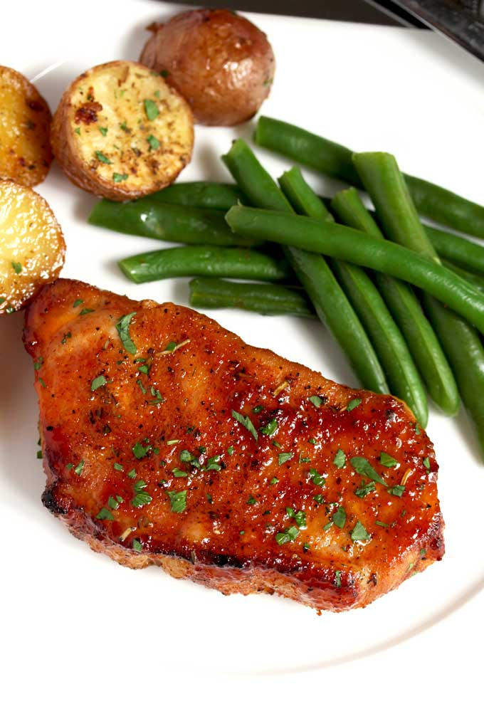 A tender seasoned chop served with roasted potatoes and green beans on a white plate.