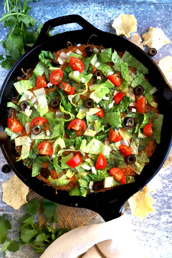 View of a skillet with taco dip topped with lettuce, tomatoes and olives.