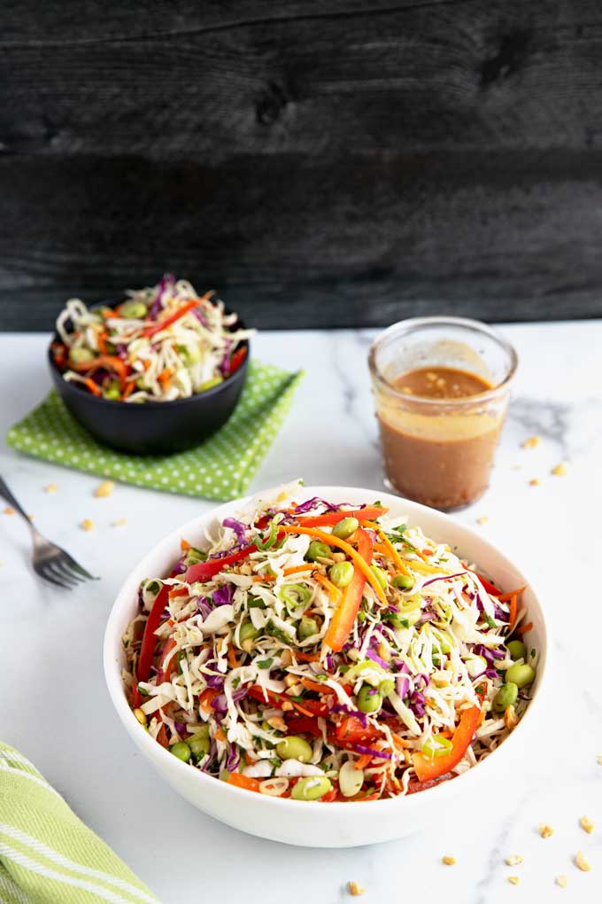 Bowls of Asian coleslaw and Peanut dressing on a white surface.