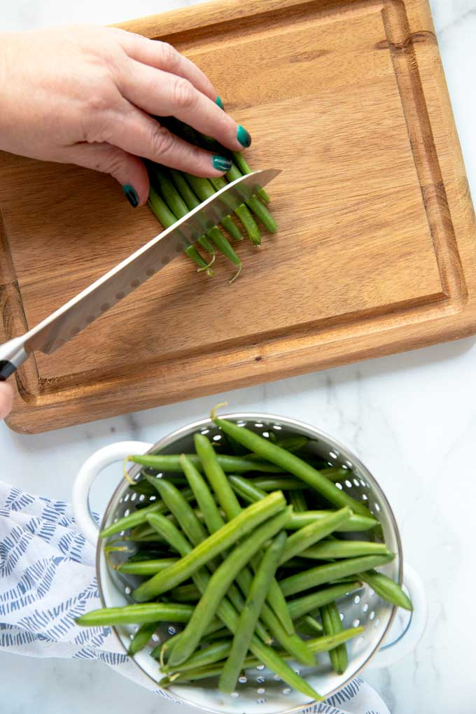 Green beans getting trimmed on a cutting board.