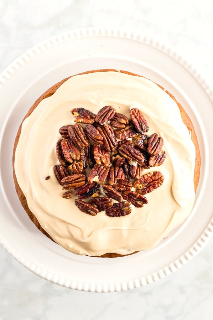 Top view of round spice cake with caramel cream cheese frosting and candied pecans