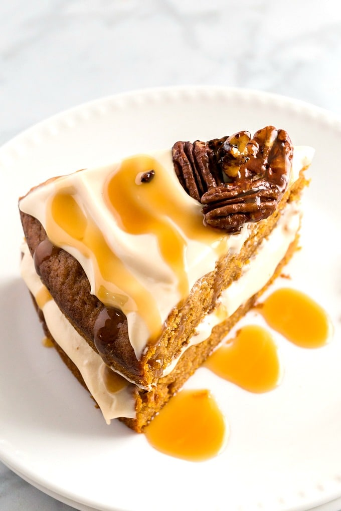 A slice of spiced cake with caramel cream cheese frosting drizzled with caramel and topped with pecans on a white plate
