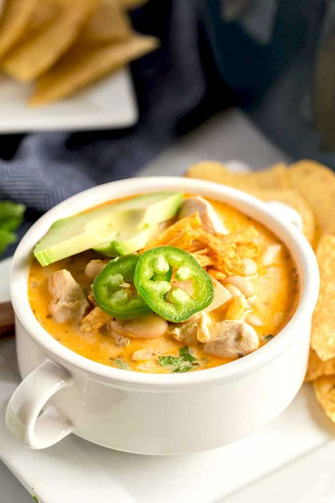 White Chicken Chili served in a white bowl and topped with cheese, tortilla chips and jalapenos.