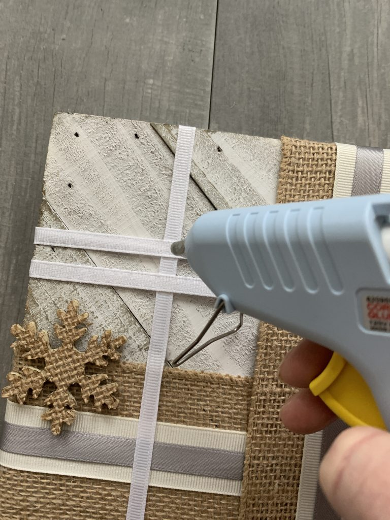 person glueing snowflake on DIY winter wall decorwith hot glue gun