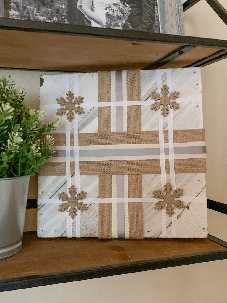 board with ribbon on shelf with plant