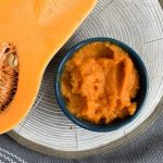 roasted butternut squash puree in bowl next to raw butternut squash