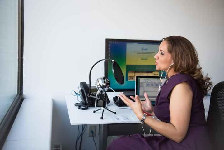 woman wearing purple dress sitting on chair near window