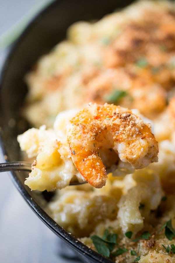 Scooping a bite of Cajun Shrimp Mac and Cheese out of a black cast iron skillet.