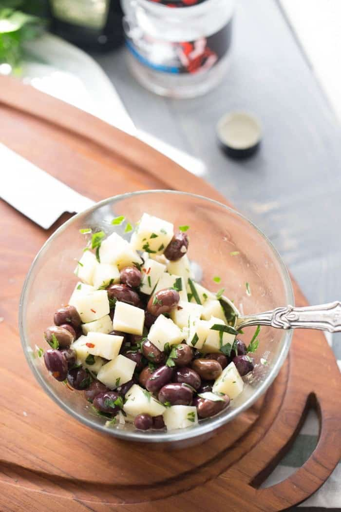 Spanish olives soak up olive oil and spices and then are tossed with manchego cheese for a piquant appetizer that is simple yet elegant.