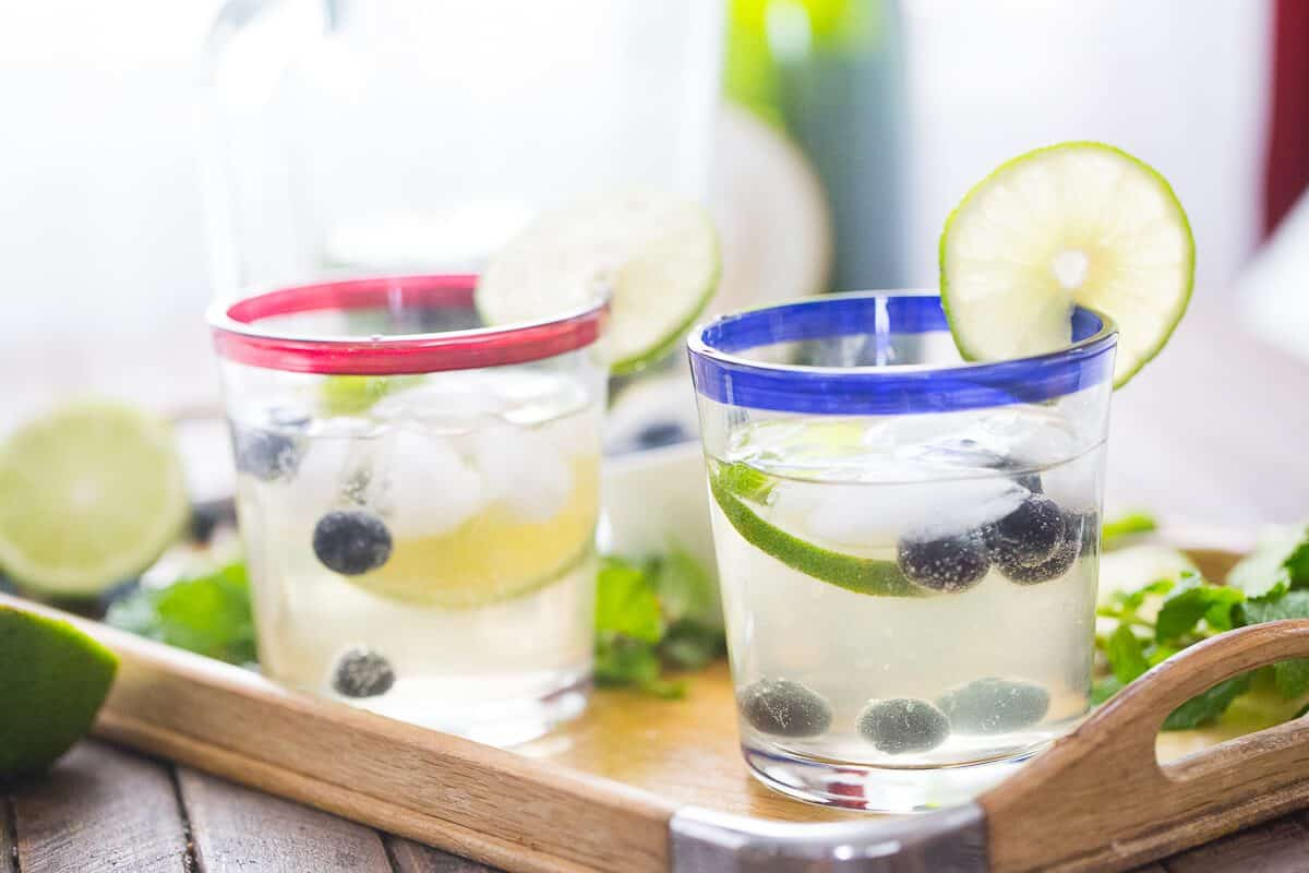 Two glasses of sweet blueberry mojitos with sliced limes, blueberries and ice on a wooden platter.