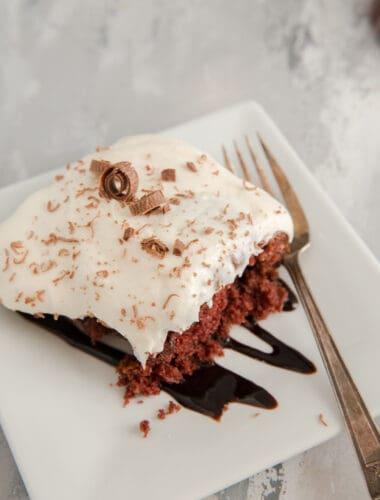 poke cake on a white plate with chocolate sauce