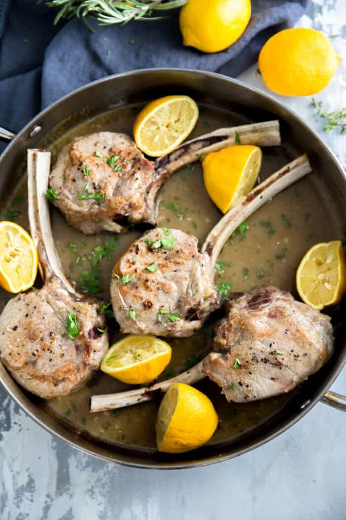 lamb chops in a pan with lemons