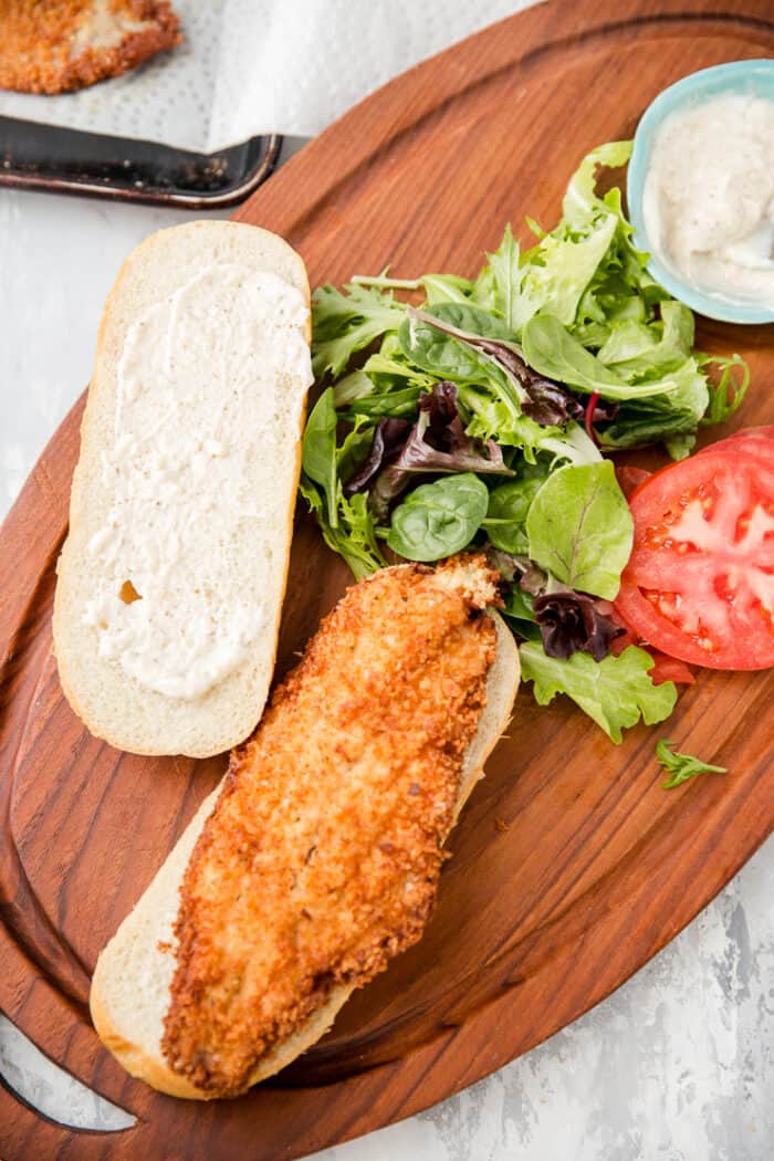 whole fried catfish resting on a sandwich bun