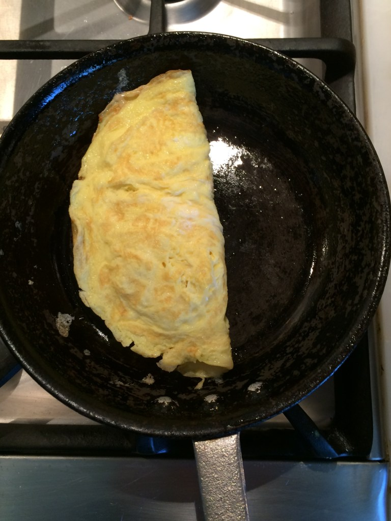 Making an omelet, fold omelet in half over cheese.