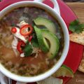 overhead picture of Mexican Chicken Soup in white bowl on red plate with sliced avocado and cilantro