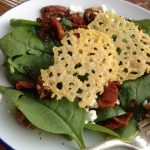 Overhead picture of spinach salad with Parmesan Crisps and crispy bacon on blue rimmed white plate.