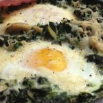 cast iron skillet with creamed spinach with eggs and bacon on top.