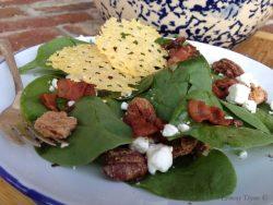 Spinach Salad with candied pecans, goat cheese, crispy bacon, and parmesan crisps on a blue rimmed white plate.